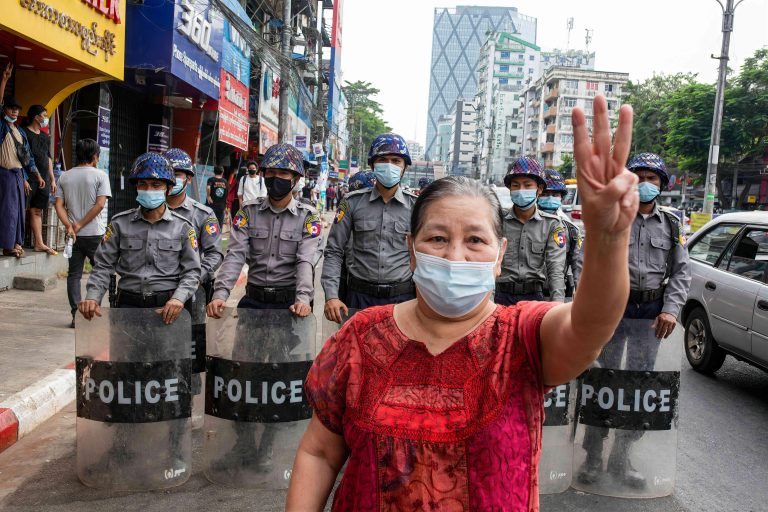 A woman in a red shirt and face mask makes a three-fingered salute in front of police officers during a demonstration.
